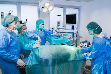 Fr. Dr. Besserer mit Assistentinnen bei einer OP. Ein Hund liegt auf dem OP Tisch